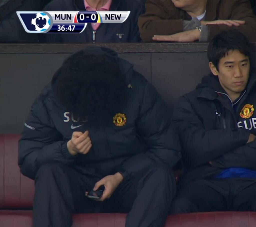 Classic Fellaini! Marouane Fellaini pictured surreptitiously using his mobile on the United bench