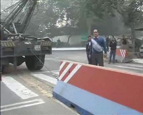 Security barricades being removed by Delhi police from outside US embassy in New Delhi as part of retaliatory measures to protest against Indian diplomat's arrest in America.