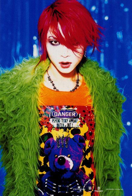 青い背景に赤い髪に緑の上着とコントラストがはっきりしているhide