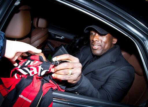 New manager Clarence Seedorf signs a Milan shirt on arrival at Rossoneri HQ