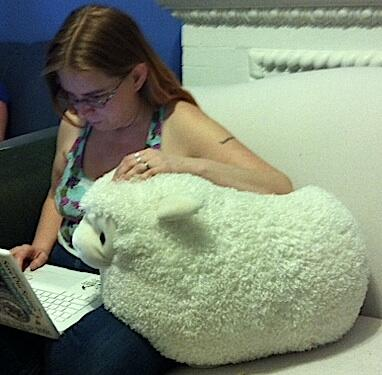 me, working on a laptop whilst leaning on a large stuffed sheep