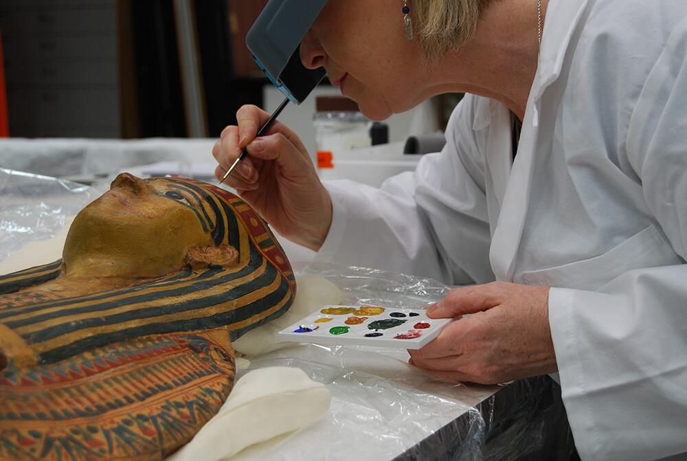 Conservator Tracy Seddon painstakingly restores the decoration on the lid of the mummy case in the studio at National Museums Liverpool.
