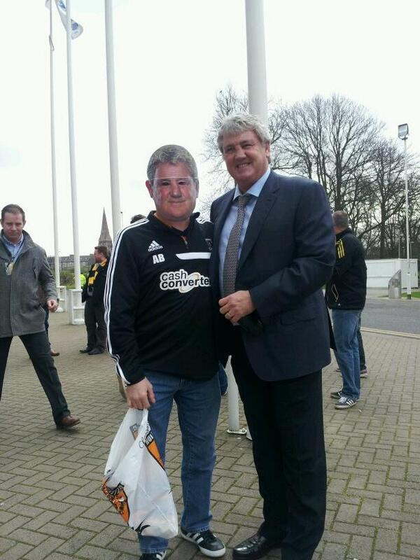 Frightening! Hull boss Steve Bruce poses for a picture with a Hull fan in a Steve Bruce mask