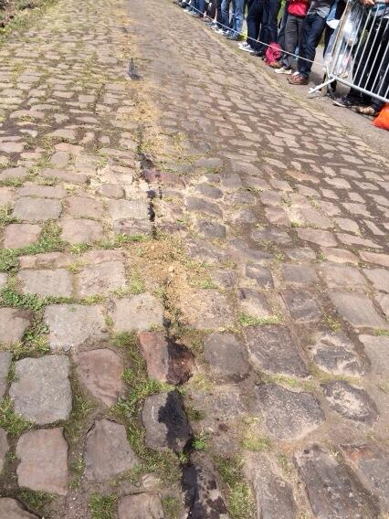 That's oil, in the middle of pave, the full length of Arenberg.  Officials trying to cover it with sand. http://t.co/itHmsof3mh