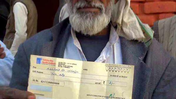 A farmer displays a cheque for Rs.2 handed out to him by Cong' s Haryana CM Hooda, as compensation for crop da... http://t.co/ZiabsyJa9i