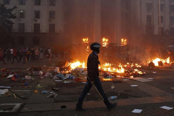 A protester walks past a fire in the trade union building in #Odessa. 40 killed in clashes: http://t.co/cce3nLoAWS http://t.co/79xSYLTtwB