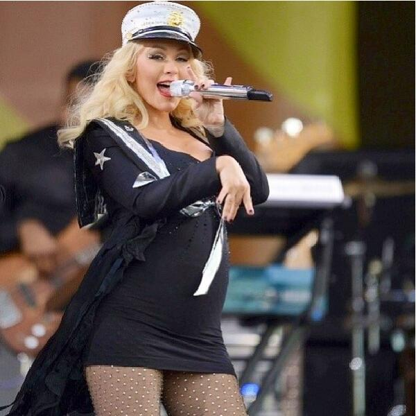 Christina Aguilera sings at a concert, wearing sheer embellished hosiery and a skin tight dress