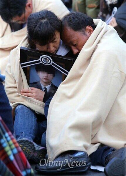 """'아들의 영정사진'  @seojuho: '꿈에서라도 만났으면..' 세월호 유가족들이 대통령면담을 요구하며 청와대입구에서 밤샘노숙. 새벽에   아들의 영정사진을 껴안고 한 부모가 잠들었다. http://t.co/rFiG6ku1wE"""""""