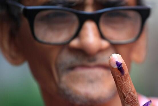 A man shows off his finger, marked with ink, to show he's voted in India's elections, 2014.   WSJ image