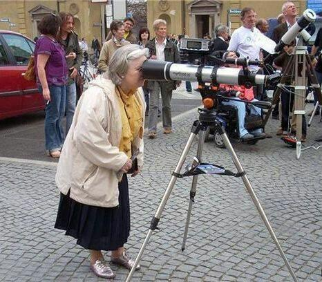 Woman looking through the wrong end of a telescope