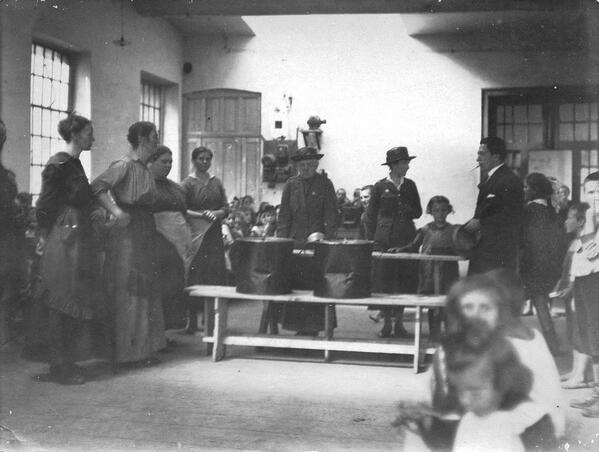 Dr. Mary Lapham (in Red Cross uniform behind table) inspects a camp for refugee children, ca 1919. #ww1archives http://t.co/OjJZoZfCJS