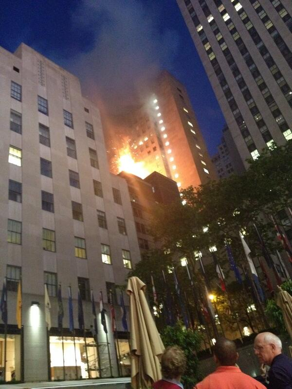 Heavy smoke & now flames shooting from the top of a building on 49th or 48th St and 5th Ave across from Rock Center http://t.co/GvuUbWjbnN