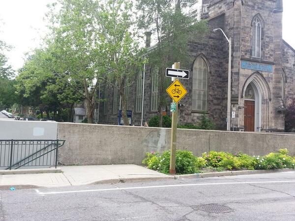 Bicycle sign at MacNab indicates eastbound route but bike lane is not continuous (Image Credit: Ryan McGreal)
