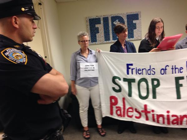 NYPD officer looks on as New York Jews occupy Friends of the IDF office in Manhattan to protest #gaza assault http://t.co/S1i7xu2DQq