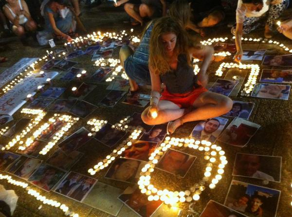 Lighting candles next to pictures of Palestinians killed in #gaza , during anti war protest in tel aviv now http://t.co/Qf4OOkGyal