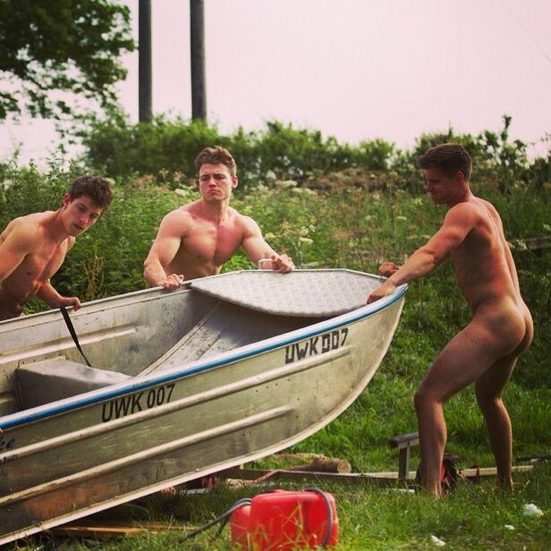 three naked men grapple with a small metal boat with the number URK 007. Taken from the Twitter feed of the Naked Rowers @naked_rowers