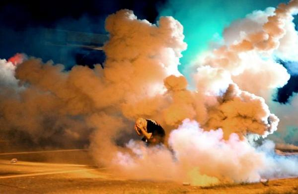 Incredible image of protester engulfed by tear gas in #Ferguson tonight. via @stltoday. http://t.co/VJdlbtJeX0 http://t.co/HXZyzrMIFq