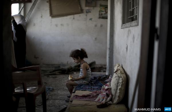 A Palestinian girl sits and eats in the rubble of her destroyed home in Gaza City by @MahmudHams #AFP http://t.co/v4ZL4Tjufw