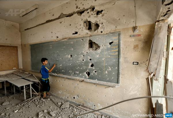 A Palestinian boy writes on a shrapnel-riddled blackboard at a school in Gaza City (via @afp) http://t.co/XvbnQFSmUd