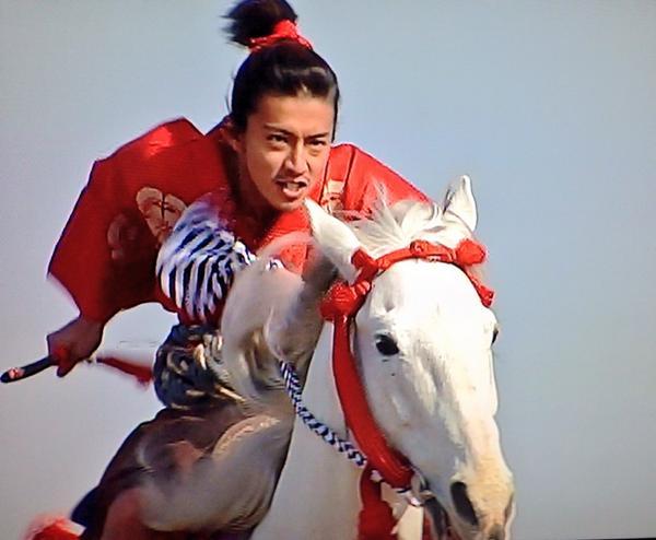 ど派手な赤い着物をきて馬を駆る木村拓哉