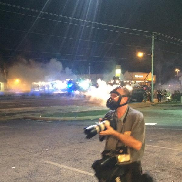 Tear gas, armored vehicles, flares. Reporters standing here with hands up so we don't get fired at. #Ferguson http://t.co/Pv9mewADWS