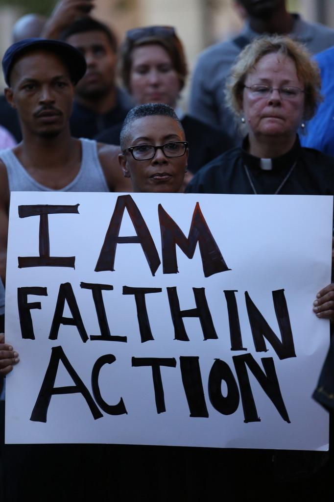 Clergy marching in Ferguson, holding a sign reading: I am Faith In Action