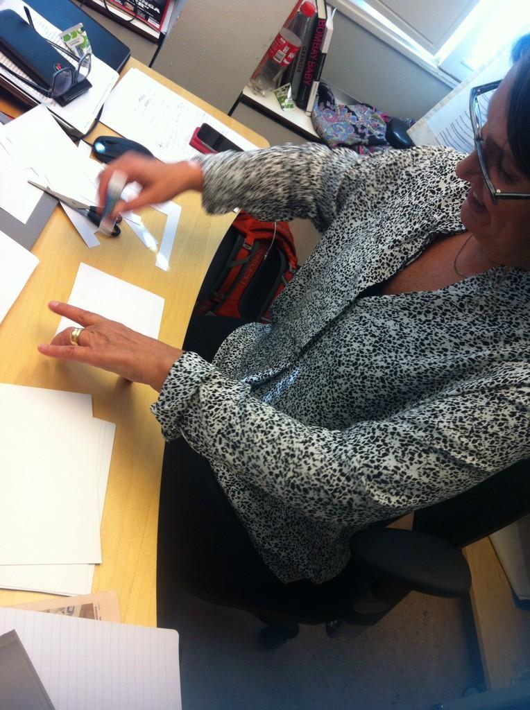 Programledare Monica Saarinen klipper och klistrar för att få ordning på manuskorten inför eftermiddagens duell.