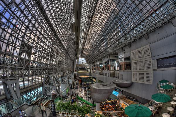 【京都・京都駅ビル】1994年の平安遷都1200年記念事業の一環。4代目駅舎として改装。原広司氏設計、地上60mの建築物。中央コンコースは4000枚のガラスを使用した正面を大屋根で覆い、吹き抜け最上部に空中経路が通っている。
