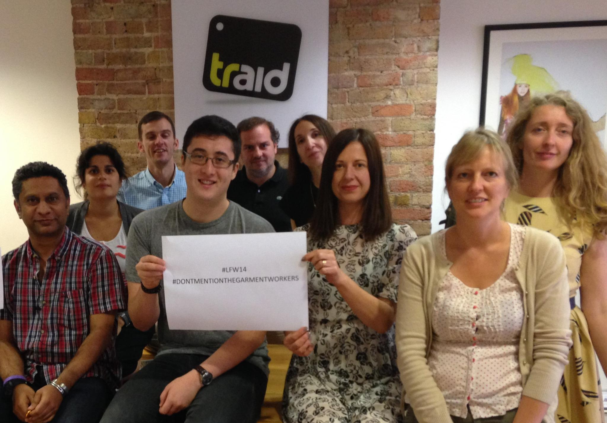 Staff at Traid Pose for a photo with the sign #DONTMENTIONTHEGARMENTWORKERS