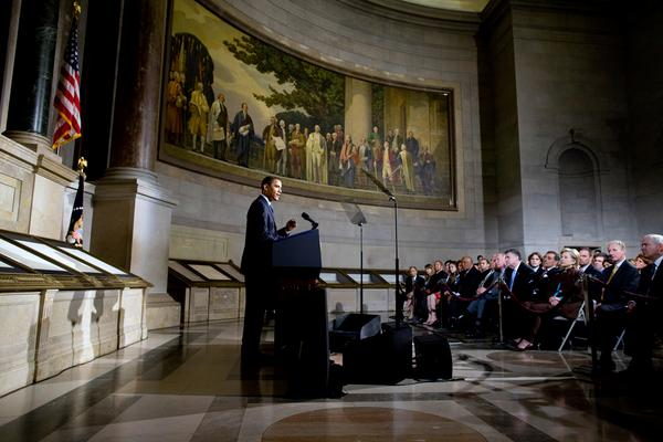 President Barack Obama literally standing with the Constitution, at the National Archives. (source of photo?)