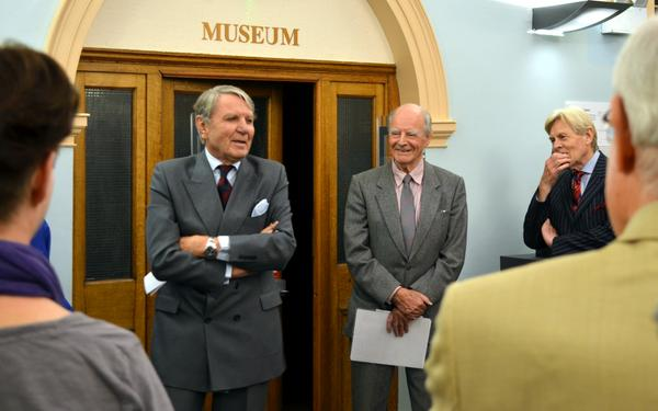 Sir Thomas Sopwith's son, Tommy Sopwith (left), unveils the bust at a ceremony in Kingston Library on 25 September 2014. Also pictured (centre) is the sculptor Ambrose Barber.