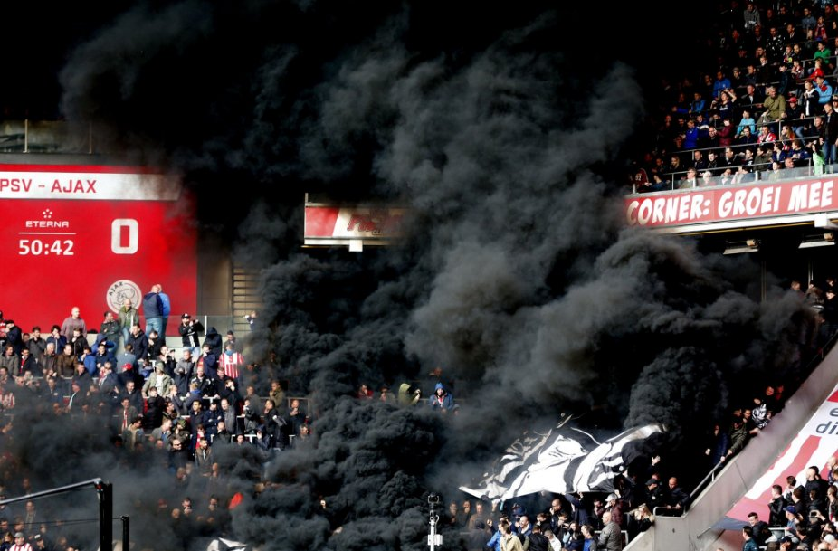 Meanwhile in Holland, black flare smoke engulfs the stands during Ajax...