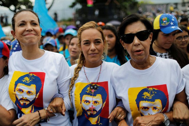 Venezuelan opposition leader Maria Corina Machado, Lilian Tintori, wife of jailed opposition leader Leopoldo Lopez and Leopoldo's mother Antonieta Mendoza, attend to a rally in Caracas on April 24, wearing tshirts with Lopez's portrait. Machado and opposition stalwart Antonio Ledezma broke with the opposition junta over its decision to participate in the gubernatorial elections.  CARLOS GARCIA RAWLINS/REUTERS