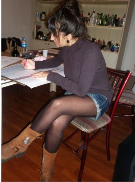 Amateur beauty at the table in her jean skirt, boots and black pantyhose
