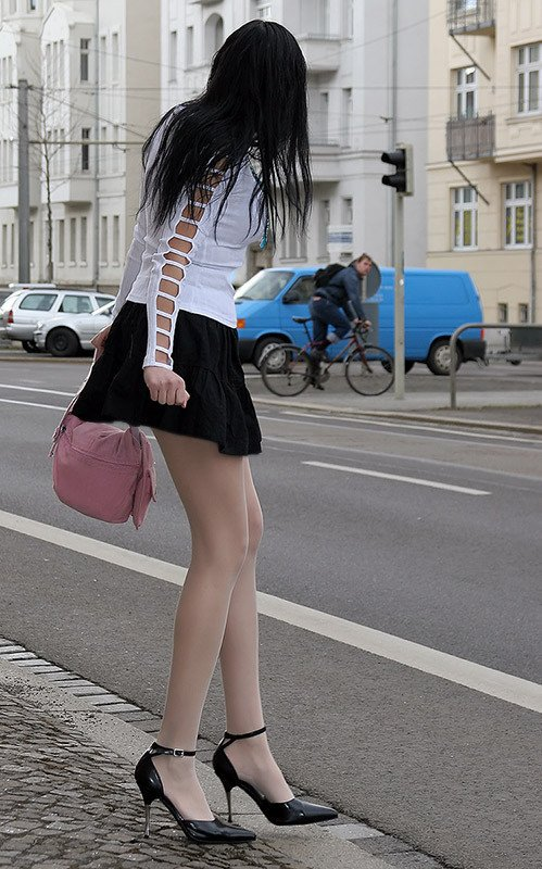 Waiting to cross the road in a short miniskirt, high heels and sheer pantyhose