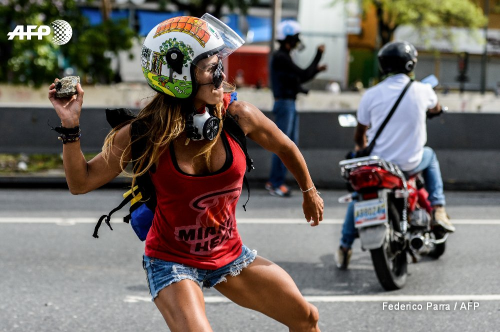 Opposition activist clashes with police during a march against Venezuelan President Nicolas Maduro on May Day in Caracas @jbarreto1974