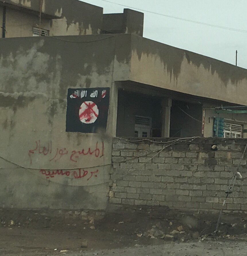 IS flag crossed out with red spray paint in Bartalla, Iraq. Text underneath: 'The Messiah is the light of the world.'