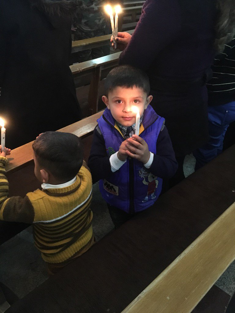 Boy holds a candle at Christmas mass in Qaraqosh, Iraq, a town recaptured from IS jihadists.