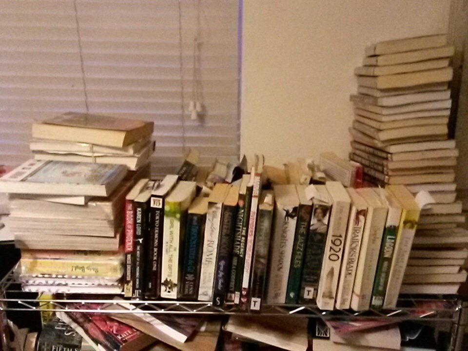 A large pile of books on top of a bookcase.