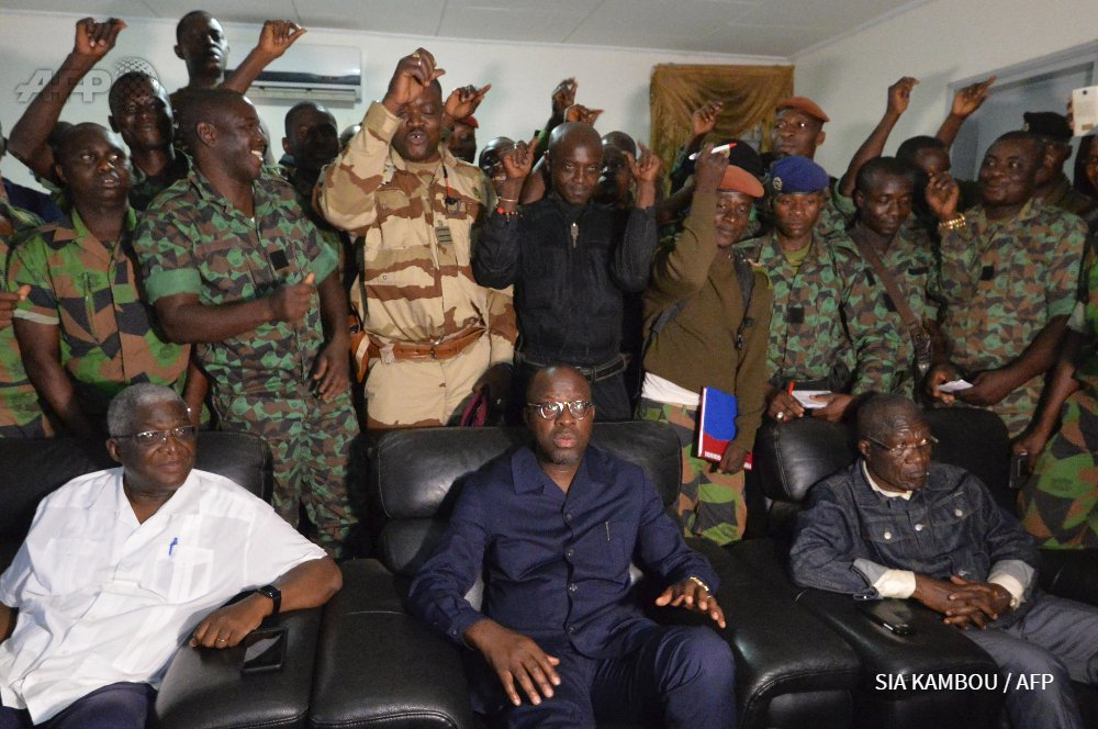 Mutinous Ivory Coast troops holding defense minister despite deal announced by president