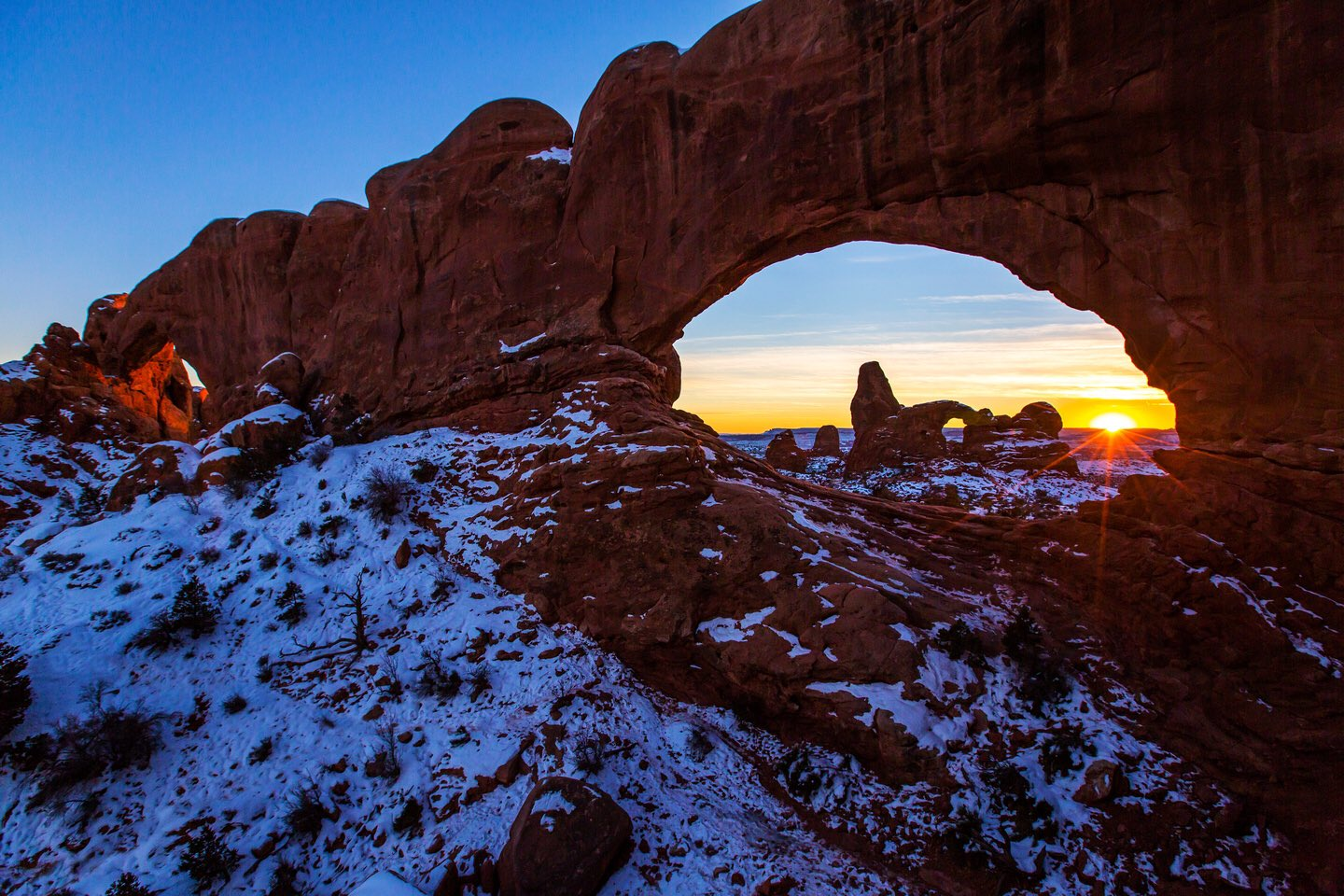 A red-rock arch appears through an arch with snow on the ground