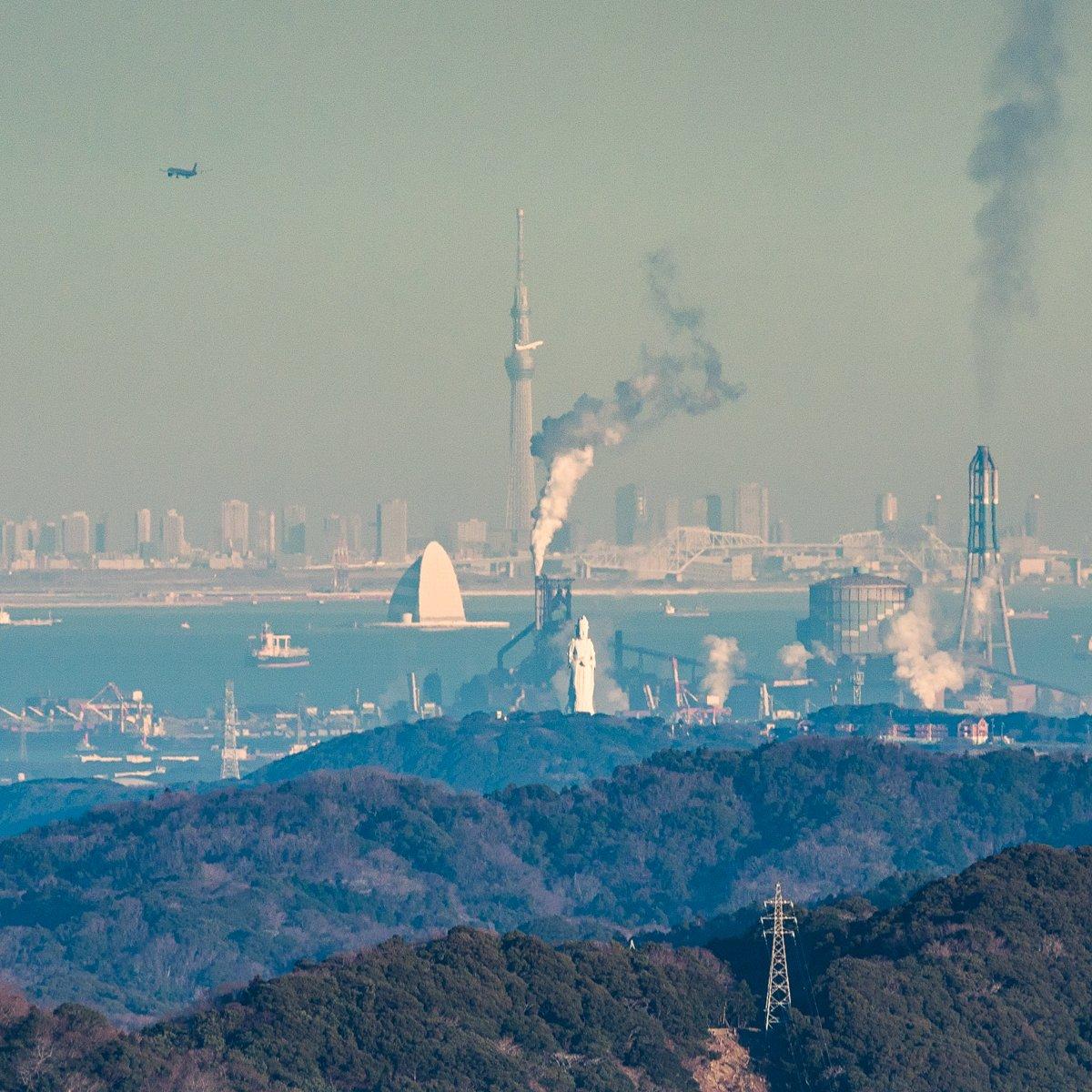 東京湾観音の背後に新日鐵住金君津工場の溶鉱炉、その背後には風の塔、そしてその背後にはジャンボジェット…