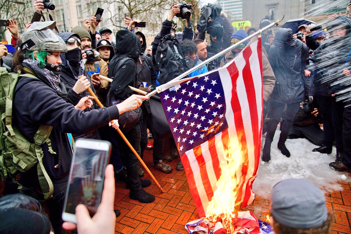 Activists are burning flags here at Pioneer Square in Portland #portland #protest #trump #InaugurationDay2017<br>http://pic.twitter.com/YQ7qYon3TL