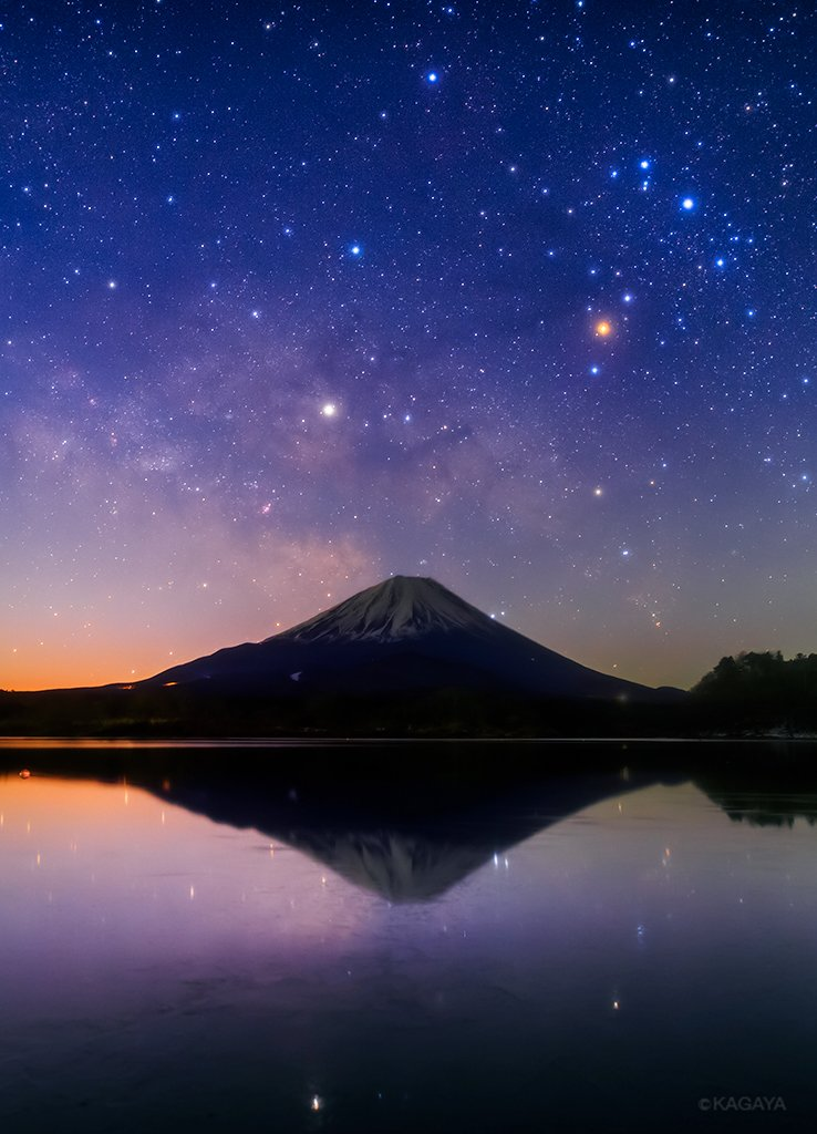 地球の夜明け、大気のグラデーションの中、天の川銀河の中心方向と富士山が重なりました。右上の赤い星はさそり座のアンタレス。中央の明るい星は土星です。撮影時、湖面に薄く氷が張り始め、この後一面薄氷で覆われました。(昨日撮影) pic.twitter.com/kOt65EvPih
