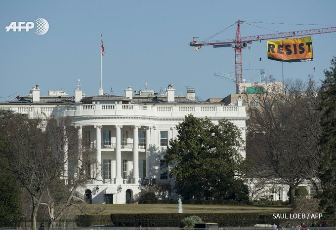 Greenpeace protesters unfold a banner reading 'Resist' from a crane behind the White House