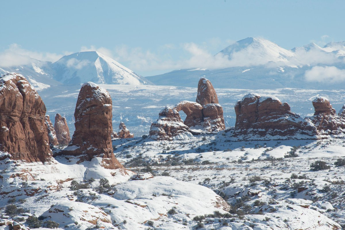 Snow covered arches and pinnacles in red sandstone, with snowy mountains in the background