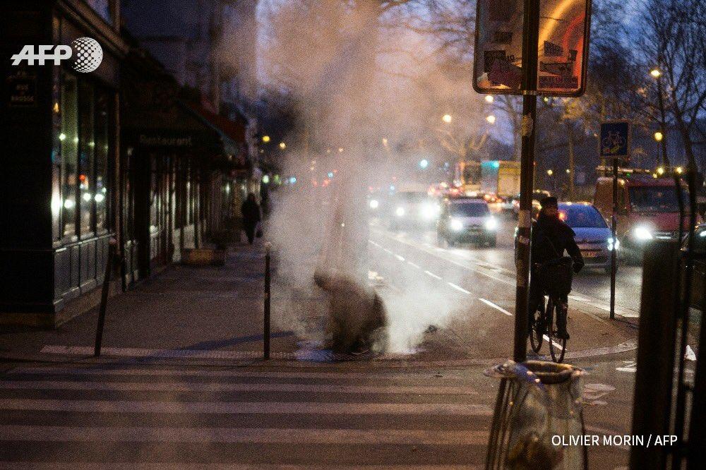 Terrible, cette image d'un homme qui se réchauffe au petit matin avec la vapeur d'une bouche d'égouts, à Paris en 2017 (Olivier Morin © AFP)