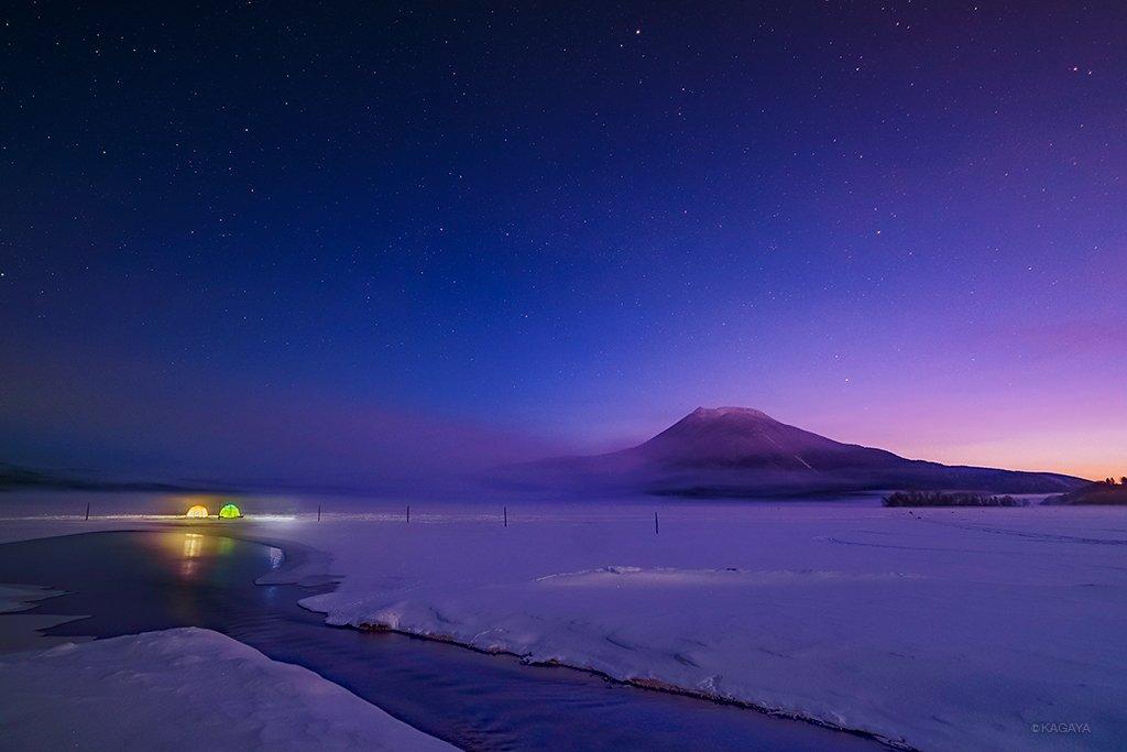 凍りついた湖の夜明け。 白い霧が通り過ぎて視界が開けると、空ではちょうど星々が薄明の暖かい色に溶けて…