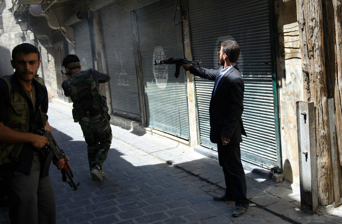 シリアでスーツ着て片手でAK撃ってる謎のおじさん。