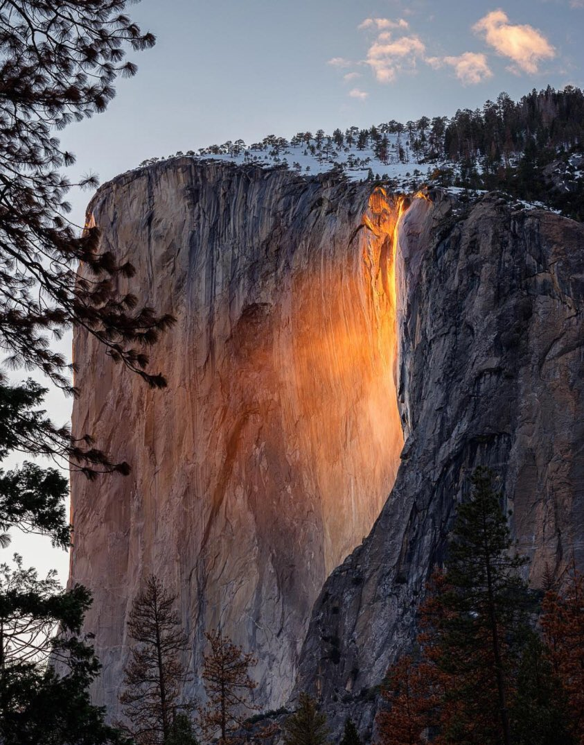 A waterfall glows orange down the side of a granite formation